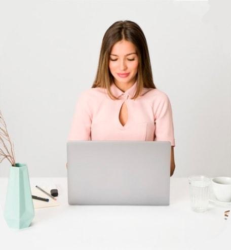 Foto ilustrativa de uma mulher utilizando um notebook referente ao atendimento online