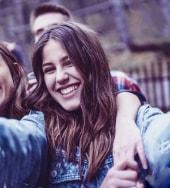 Foto ilustrativa de uma adolescente tirando foto com seus amigos ao fundo