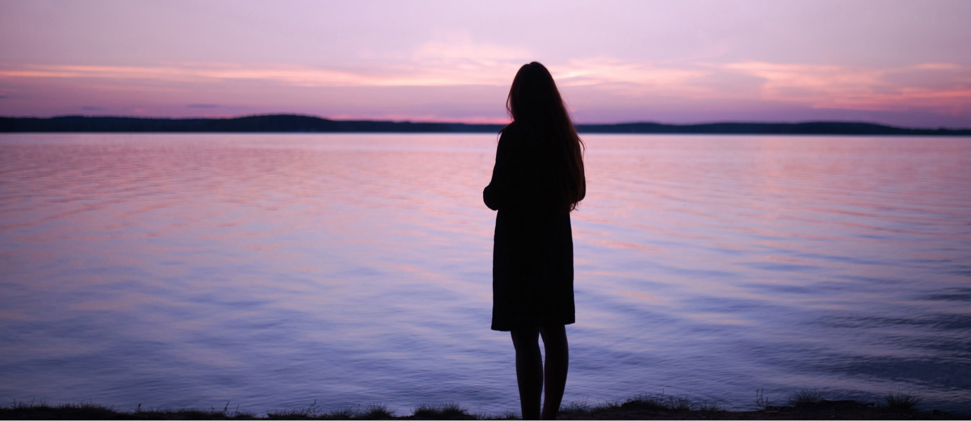 Foto ilustrativa de uma mulher olhando um lago